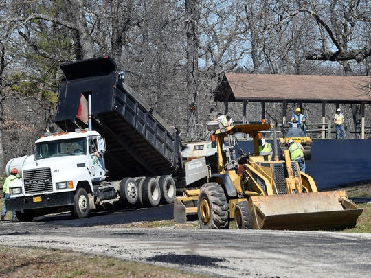 Employees with Marion County Paving work Monday resurfacing
