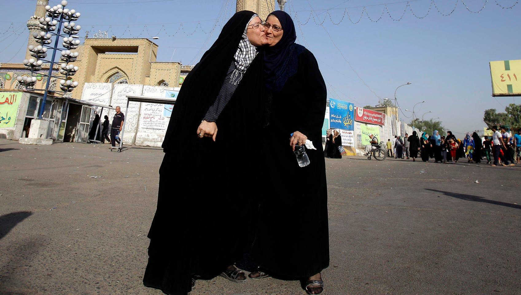 Women exchange greetings after dawn prayers outside the Abu Hanifa Mosque in Azamiyah, Iraq.