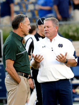 Head coach Mark Dantonio, left, talks with Irish head coach Brian Kelly before the start of the Spartans game against Notre Dame Saturday, Sept. 17, 2016 in South Bend, Ind.