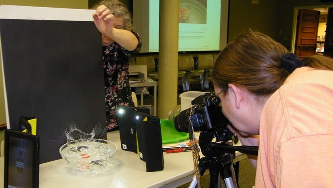 Judy Soper practices taking a photo using the drop splash technique while Clyde Library Adult Services Librarian Jill McCullough drops an object in the water during a meeting of Clyde Photography Club.