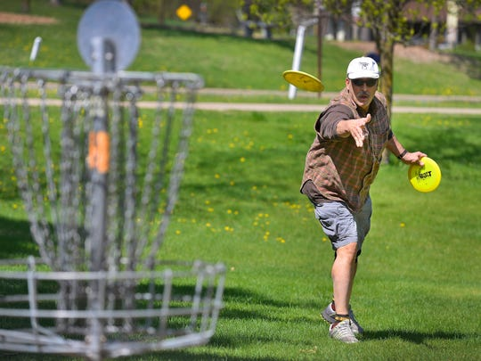 James Ferkinhoff makes a put while playing disc golf Wednesday at Calvary Hill Park in St. Cloud.
