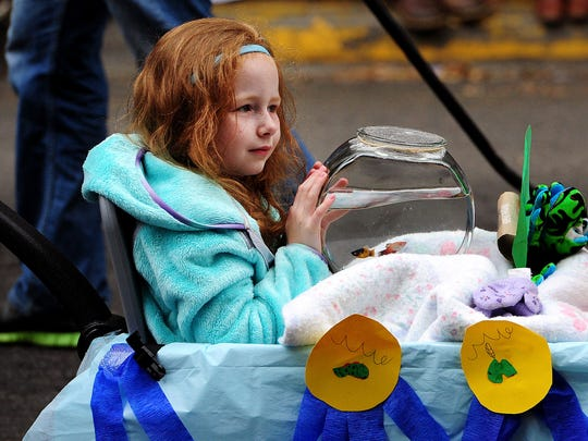 Laura Werch, 7, of Silverton, rides along with her fish Saturday during the Silverton Pet Parade.