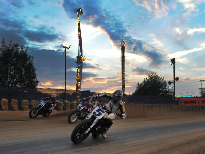 Jake Johnson  leads a pack of bikes out of turn four  and the lights of the midway during the AMA Indy Mile Flat track race,  Friday Aug.8, 2014 at The indiana State Fairgrounds