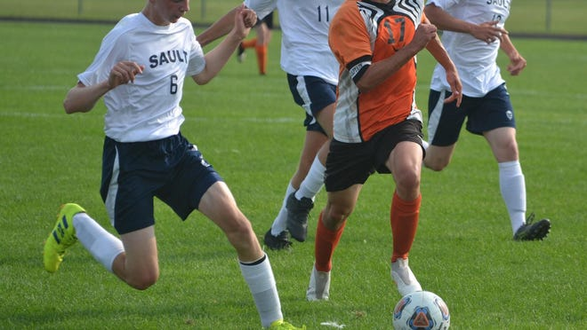 Cheboygan senior midfielder Ethan Lindle (17) chases for the ball against Sault Ste. Marie's Denvey McCord (6) during the first half of a varsity boys soccer matchup in Cheboygan on Monday. Lindle scored the opener for the Chiefs, who rolled to a 6-0 victory in their season opener.