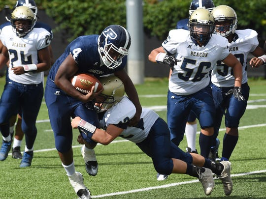 Poughkeepsie's Joel Perez, left, gets tackled by Beacon's William Rivera, right, during Saturday's game.