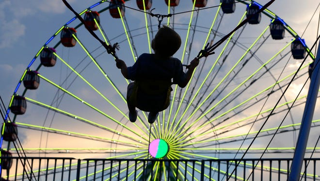 Gavin Magee, 3, Oak Creek enjoys a trampoline jumping into the air at the Wisconsin State Fair on Aug. 3.