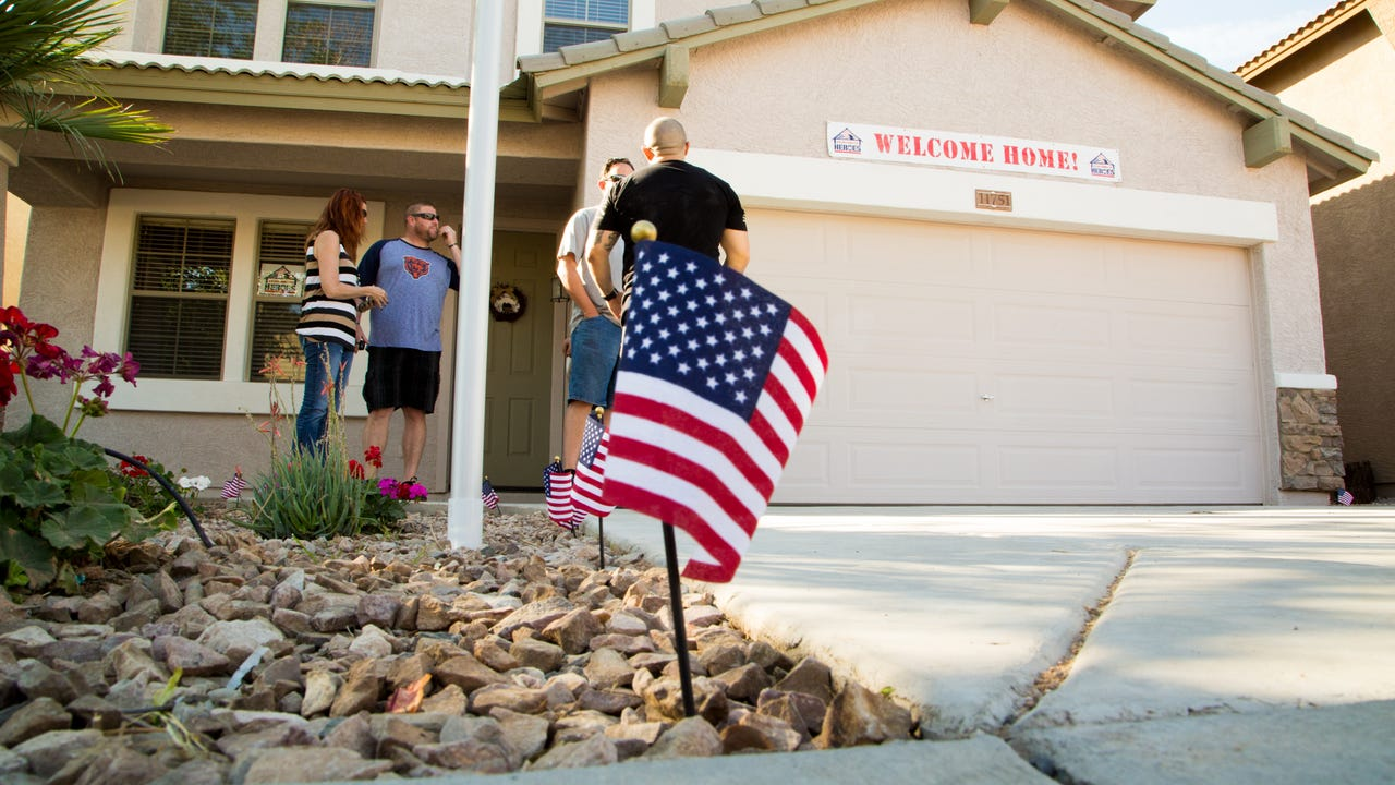 Army Spc. Alexis Jacquez Gamez, his wife, Mariana Gamez, and family get the keys to a mortgage-free home on March 21, 2017, thanks to Building Homes for Heroes and JP Morgan Chase Bank. April Morganroth/azcentral.com