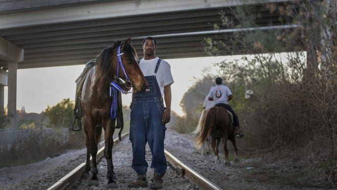 Elgin farrier Korey Jones stands with his horse Miss Daisy under the bridge of U.S. 183 during a trail ride Dec. 14, 2019, in East Austin. Jones is a part of a trail riding group called JamDine Boyz out of Elgin. The group has been together for two years and is among several trail riding groups in Elgin and Austin. Jones, who is known for his farrier services, is self-taught and has built a successful business trimming and shoeing horses.