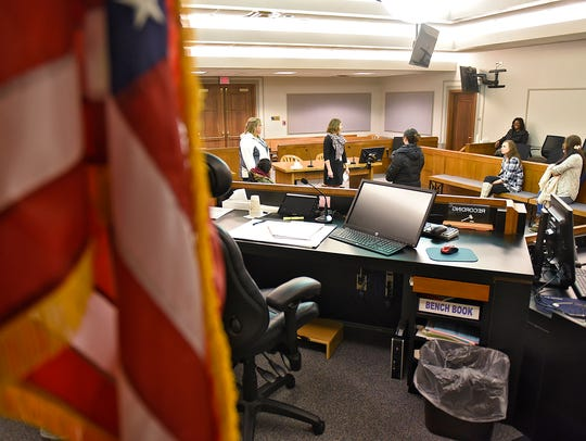 People take a tour of one of the courtrooms Thursday,
