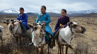 Three young members of the East Taiga community of Tsaatan reindeer herders show off their riding skills.
