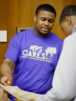 Kalan Haywood II, president of the Milwaukee Youth Council, explains some of its programs to a Milwaukee Public Schools student at a special event for MPS CARES, a new initiative to expand recreation and civic engagement opportunities for young people.