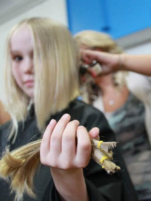 Third grader Katelyn Scherf holds locks of her hair during a large Locks of Love event at Clear Creek Elementary in Oxford on Wednesday, April 9, 2014.