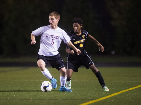 Gettysburg's Zach Shoemaker and Lancaster Mennonite's Matthew Lynch battle for the ball during Thursday's District 3 Class AA boys' soccer championship.