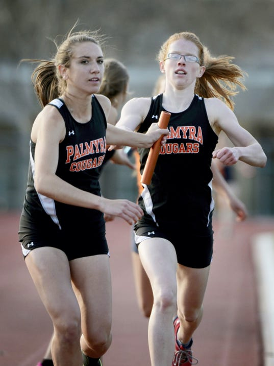 Palmyra's Ellie Keck, right, hands the baton off to Katie Dembrowski for the final leg of the 1600 meter relay. The Cougars won the event to close out a 98-52 victory over Hershey.