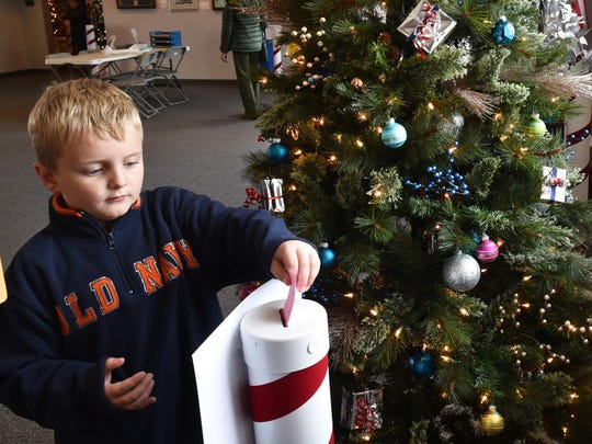 Michael Martell of Sturgeon Bay places his vote last year for the tree he would like his family to win in a raffle during the opening of last year's Merry-Time Festival Of Trees at the Door County Maritime Museum in Sturgeon Bay.