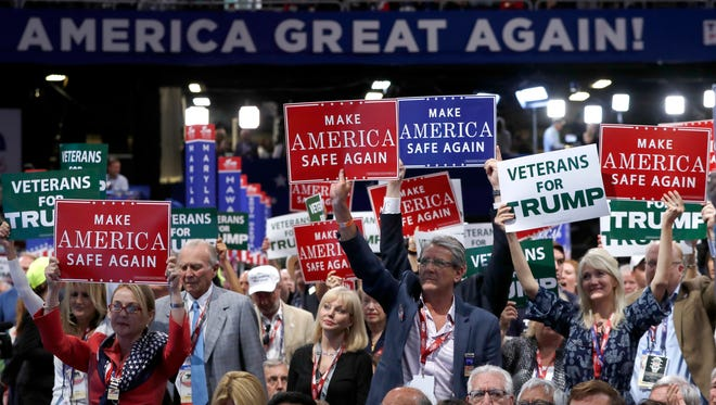 Delegates hold up signs and cheer during first day of the Republican National Convention this week in Cleveland, Ohio.