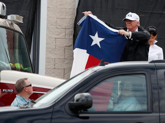 President Donald Trump, accompanied by first lady Melania Trump, holds up a Texas flag after speaking with supporters outside Firehouse 5 in Corpus Christi, Texas, Tuesday, Aug. 29, 2017, following a briefing on Harvey relief efforts. (AP Photo/Evan Vucci)