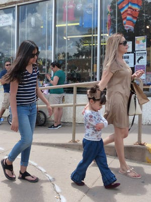 One little visitor seems discontented shopping with her mother in Ruidoso..