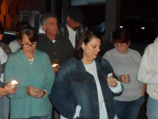 Those attending a vigil for the victims of the terrorist attacks in Paris hold candles as they listen to a speaker Sunday in downtown Alexandria.