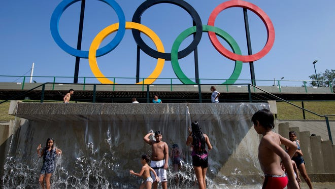 Children play in a water fountain next to Olympic rings at Madureira Park in Rio de Janeiro, Brazil.