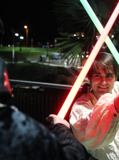 Rob Kimbrough as Luke Skywalker duels with Lanny Thomas as Darth Vader as they pose for a photo at Cascades Park.