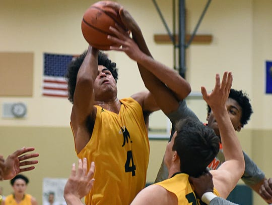 Manogue's Curtis Luckadoo goes up for a rebound against