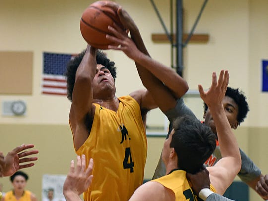 Manogue's Curtis Luckadoo goes up for a rebound against Bishop Gorman in the Wild West Shoot Out tournament at Bishop Manogue High School on Thursday.