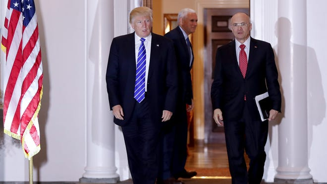 President-elect Donald Trump and Andy Puzder, chief executive of CKE Restaurants, walk from Trump National Golf Club Bedminster clubhouse in Bedminster, N.J., Saturday, Nov. 19, 2016. In the background is Vice President-elect Mike Pence.