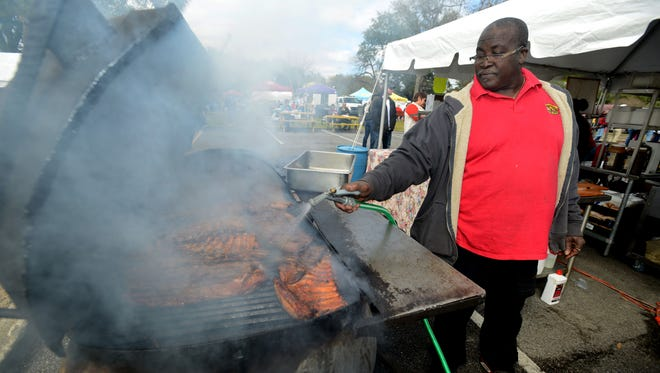 Denby Williams with Arlene Williams Bar-B-Que spritzes the grill while checking on some ribs last year during Smokin' in the Square at Seville Square.