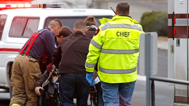 Emergency medical technicians rush one of two shooting victims to an ambulance after they were shot in an office in Moscow, Idaho, on Saturday, Jan 10, 2015.