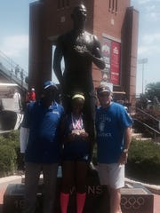Alysse Wade with her three gold medals and coaches Bruce Woodson and Dan Schlitt in front of the Jesse Owens statue outside Jesse Owens Memorial Stadium in Columbus.