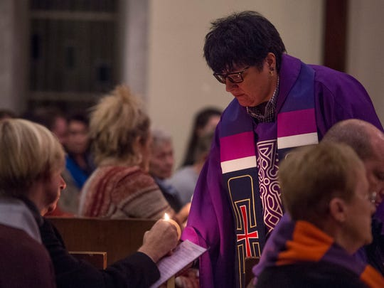 University chaplain Tamara K. Gieselman lights candles during the 40th Anniversary Commemoration of the 1977 UE Plane Crash at Neu Chapel in Evansville, Ind., on Wednesday, Dec. 13, 2017.