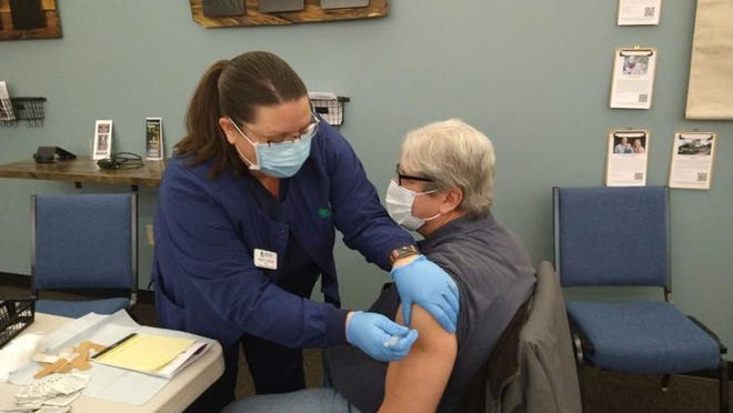 Tracy Tonsor (left), a nurse with the Health Department of Northwest Michigan, administers the first dose of the COVID-19 vaccine to Herald Times reporter Paul Welitzkin Wednesday in Gaylord.
