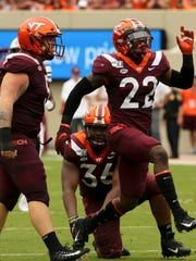 Virginia Tech defender Chamarri Conner (22) celebrates a sack of Furman quarterback Darren Grainger with teammates Jarrod Hewitt (5) and DaShawn Crawford (36) during the first half of an NCAA college football game, Saturday, Sept. 13, 2019, in Blacksburg Va. (Matt Gentry/The Roanoke Times via AP)
