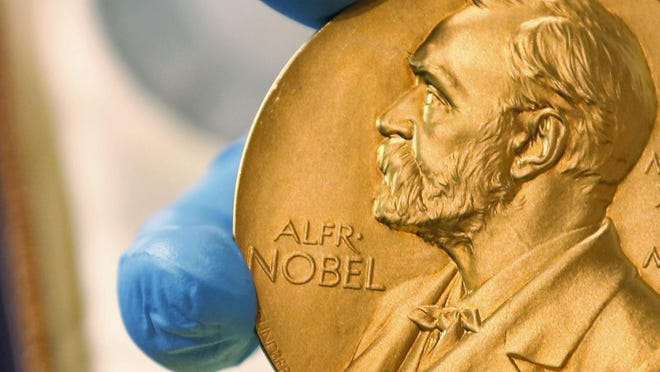 FILE- In this April 17, 2015, file photo a national library employee shows the gold Nobel Prize medal awarded to the late novelist Gabriel Garcia Marquez, in Bogota, Colombia.