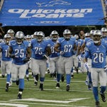 Detroit Lions running back Mikel Leshoure (25) runs on to Ford Field with teammates offensive guard Larry Warford (75), guard Rob Sims (67) and strong safety Don Carey (26).