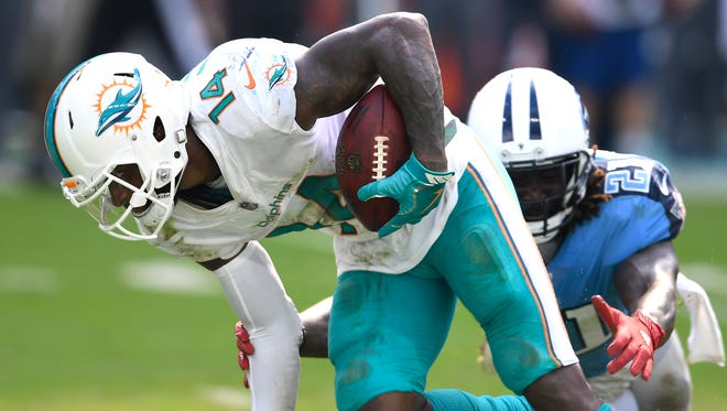 Dolphins wide receiver Jarvis Landry (14) races up the field with a first-down catch as Titans safety Da'Norris Searcy (21) tries to stop him during the fourth quarter at Hard Rock Stadium Sunday, Oct. 8, 2017 in Miami Gardens, Fla.