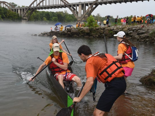 Two competitors prepare to jump into their canoe as