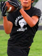 Aloysius Comanche catches a pass during practice on Wednesday.