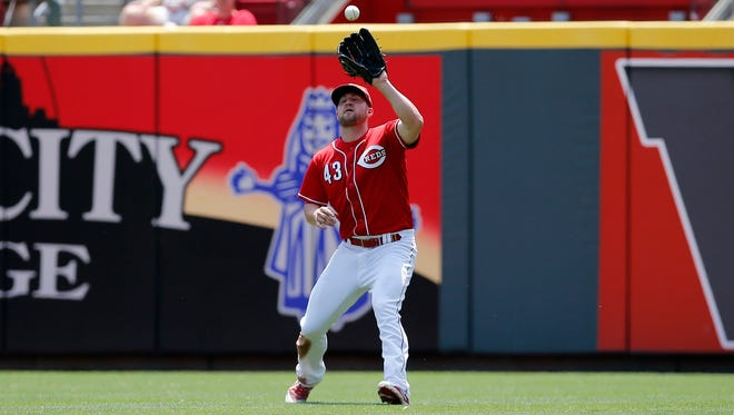 Cincinnati Reds right fielder Scott Schebler (43) catches a fly ball off the bat of Colorado Rockies third baseman Ryan McMahon (24) in the top of the second inning of the MLB National League game between the Cincinnati Reds and the Colorado Rockies at Great American Ball Park in downtown Cincinnati on Thursday, June 7, 2018.