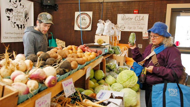 Bret Morris of Shared Roots Farms helps Heather Kirkland of Apalachin as she purchases produce during the Broome County Regional Farmers Market at 840 Front Street, Binghamton on Saturday, December 2, 2017. 