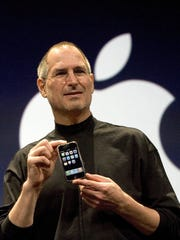 """Apple CEO Steve Jobs holds up the new iPhone that was introduced at Macworld on Jan. 9, 2007, in San Francisco. During the keynote Jobs introduced the new iPhone which combined a mobile phone, a widescreen iPod with touch controls and a internet communications device with the ability to use email, web browsing, maps and searching. Jobs claimed the phone ran OS X and """"desktop applications."""" The operating system was renamed """"iPhone OS."""""""