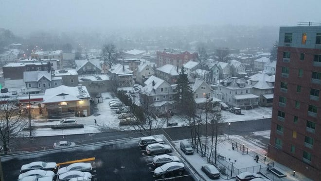 Light layer of snow covers cars and houses in White Plains Dec. 11.