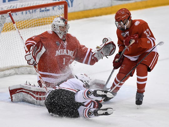 St. Cloud State's Robby Jackson slides past Miami goaltender