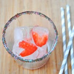 A sugar-rimmed cocktail glass with strawberry ice cubes.