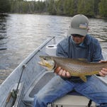 Chris Lessway holds up his catch from a recent fishing trip on the Au Sable River.