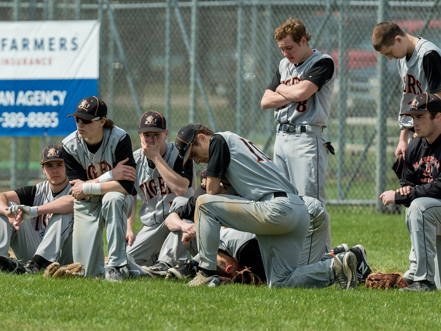 The Marshfield High School baseball team reacts Saturday after teammates Trevor Schwecke, 17, and Braden Bohman, 15, collided during a game against Chippewa Falls at Jack Hackman Field in Marshfield.
