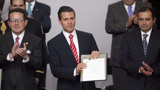 Enrique Pena Nieto, center, seeks to make Mexico more democratic and competitive in the world economy. AP FILE - In this March 11, 2013 file photo, Mexico's President Enrique Pena Nieto, center, is flanked by Mexican Senate Deputy Chairman Francisco Arroyo Vieira, left, and Mexican Senate President Ernesto Cordero as he shows an agreement signed by him and the three major political parties that would create two new national television stations and form a powerful independent regulatory commission, along the lines of the U.S. Federal Communications Commission, in Mexico City. Pena Nieto has been fast out of the blocks in attacking some of Mexico's toughest issues in a country often stymied by monopolies and corruption. He says his plan will make the country more democratic and competitive in the world economy, and his drive for reform is fueling international confidence about Mexico. (AP Photo/Alexandre Meneghini, file)