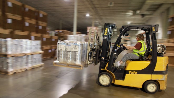 Lisa Carson, a forklift operator at Verst Group Logistics in Walton, unloads pallets of plastic wrap  from a truck at the company's   warehouse. The demand for jobs in transportation, distribution and logistics continues to grow.
