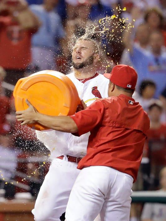 St. Louis Cardinals' Matt Adams, left, is splashed by teammate Kolten Wong as Adams arrives at home plate after hitting a walk-off home run to defeat the Los Angeles Dodgers 4-3 in the 16th inning of a baseball game early Saturday, July 23, 2016, in St. Louis. (AP Photo/Jeff Roberson)
